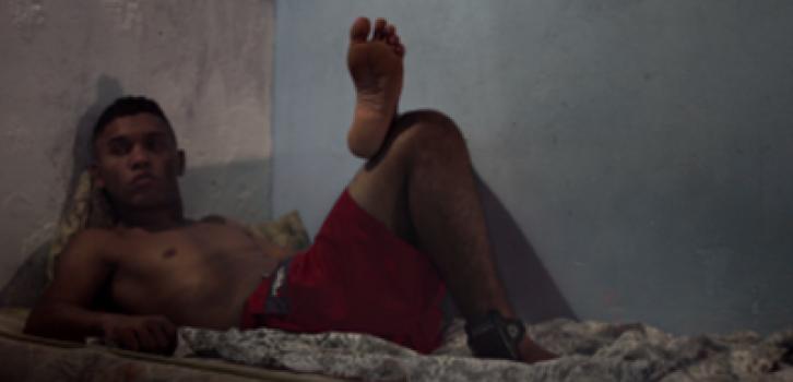 Cena do filme, Ivan está deitado em um colchão com a tornozeleira de monitoração eletrônica