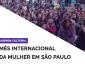 A imagem contem os títulos agenda cultural e mês internacional da mulher em são paulo em fundo branco, dentro de um triângulo no canto superior direito tem a foto de mulheres em uma manifestação.
